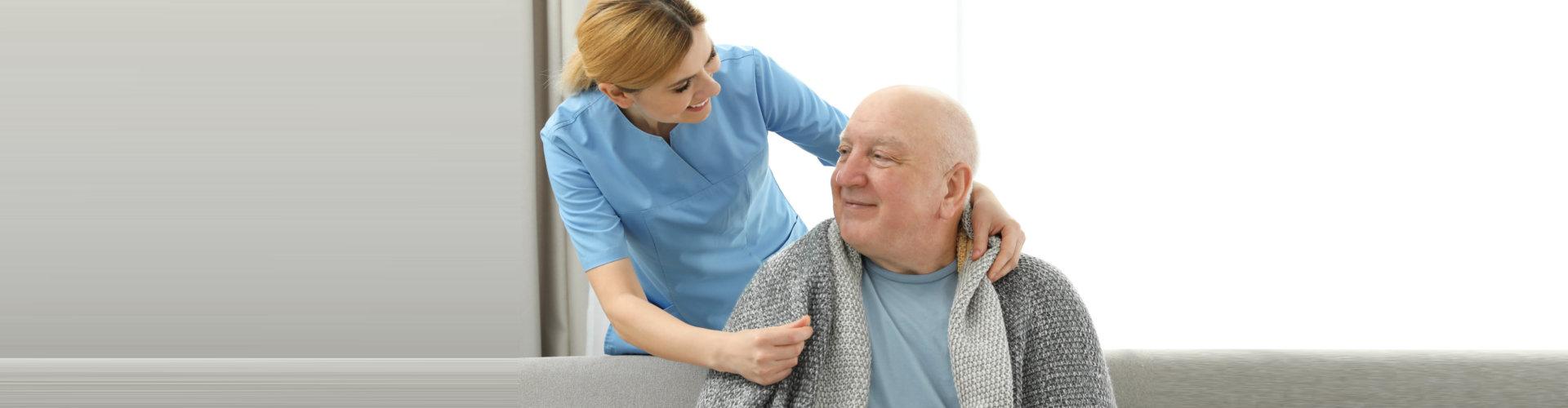 a nurse giving a senior a blanket